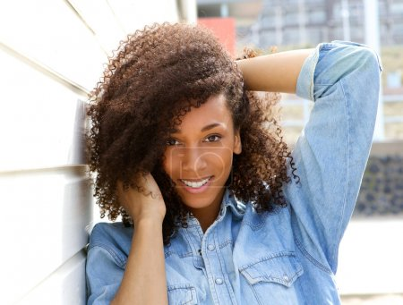 Photo for Close up portrait of a happy african american woman smiling outdoors with hand in hair - Royalty Free Image