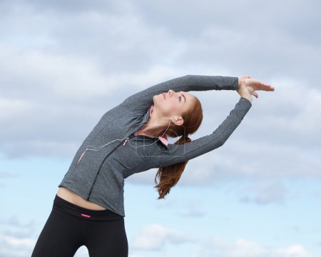 Young woman doing stretch exercises outdoors
