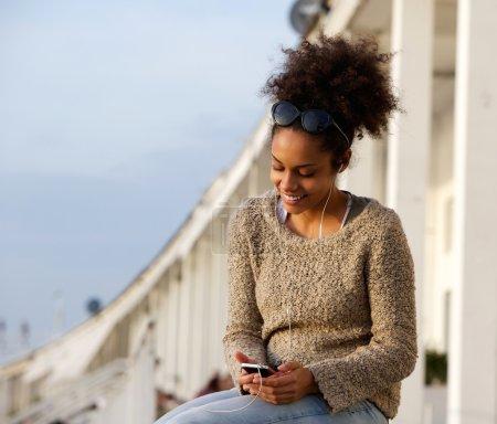 Photo pour Portrait d'une jeune femme souriante à l'extérieur avec téléphone portable et écouteurs - image libre de droit