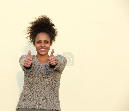 Photo pour Portrait d'une jeune femme souriante avec les pouces vers le haut signe - image libre de droit