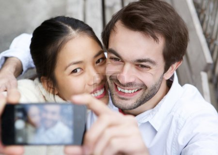 Happy young couple taking a selfie and smiling