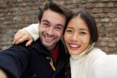 Happy smiling young couple taking selfie