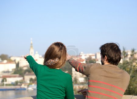 Young man and woman pointing finger in the distance