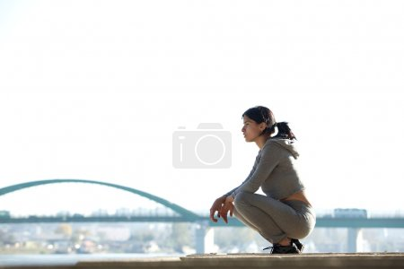 Sporty young woman sitting outdoors