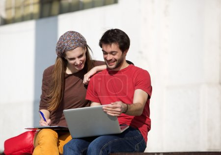Two university students studying with laptop outdoors