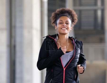 Smiling young woman running outdoors with earphones