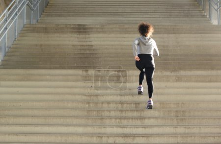 Young female athlete running up stairs
