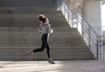 Healthy young woman running in urban environment