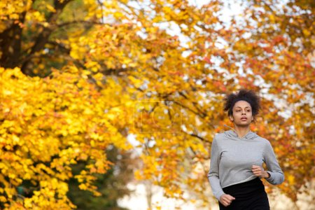 Photo for Portrait of a young woman jogging outdoors in the park - Royalty Free Image