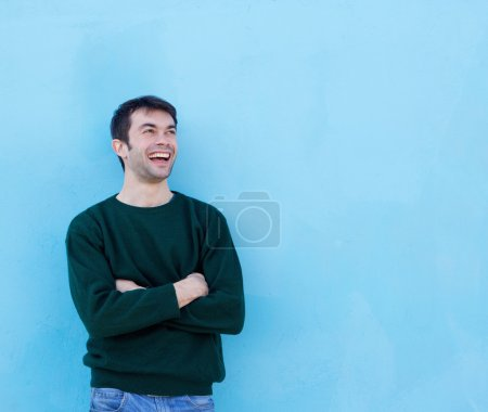 Happy young man laughing against blue background