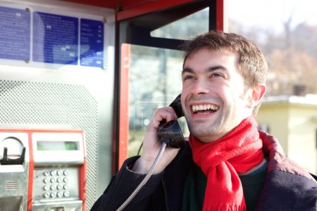 Young man calling from phone booth
