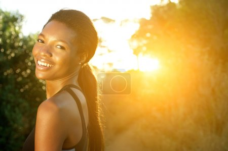 Attractive young sports woman smiling outdoors