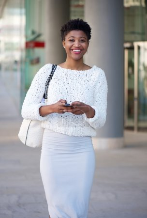 Photo for Portrait of a happy young african american woman sending text message on cellphone - Royalty Free Image