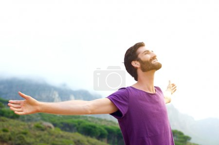 Happy young man standing in nature with arms spread open