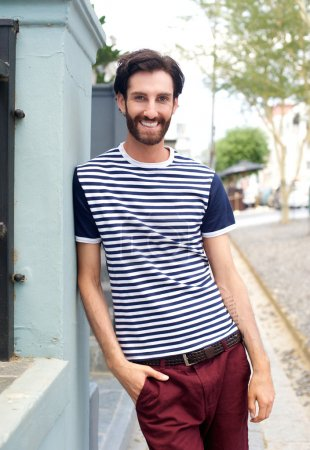 Photo for Portrait of a happy trendy man in striped shirt leaning against wall outdoors - Royalty Free Image