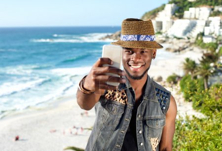 Handsome man taking selfie while on vacation at the beach