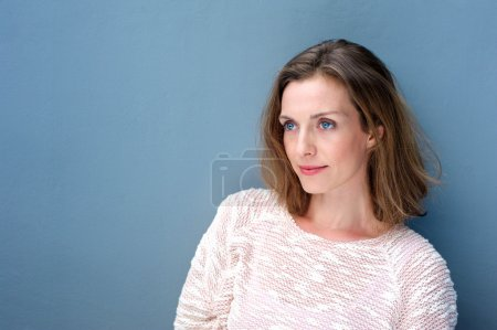Photo for Close up portrait of a charming woman in sweater posing on blue background - Royalty Free Image