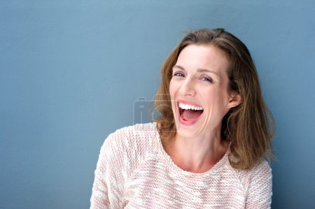 Photo for Close up portrait of a happy beautiful fresh mid adult woman laughing on blue background - Royalty Free Image