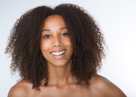 Young african american woman smiling with curly hair