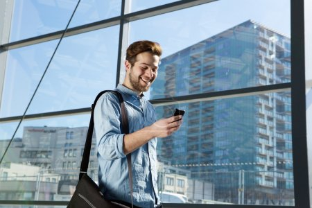 Attractive young man walking and looking at mobile phone