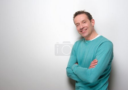 Relaxed middle aged man smiling with arms crossed