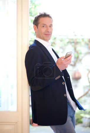 Confident businessman holding mobile phone