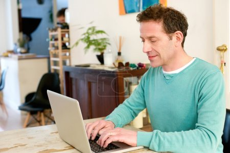 Mature male adult sitting at table at home using laptop