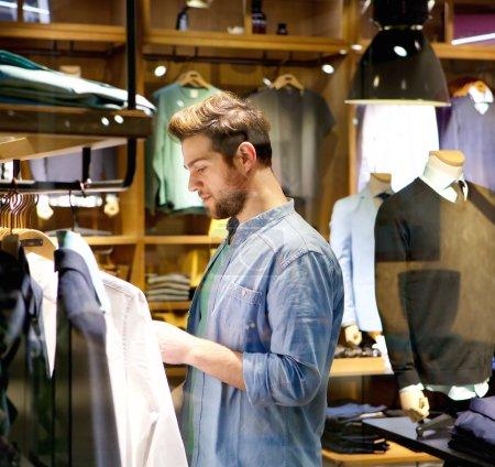 Photo pour Portrait d'un beau jeune homme faisant du shopping pour des vêtements à la boutique - image libre de droit