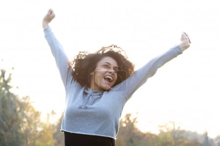 Carefree young woman smiling with arms raised