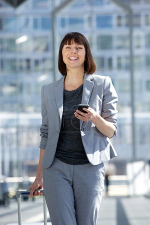 Professional business woman traveling with bag and mobile phone