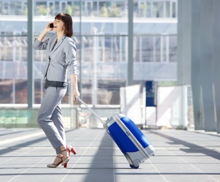 Foto de Full length side portrait of a happy business woman walking with suitcase and talking on mobile phone at airport - Imagen libre de derechos