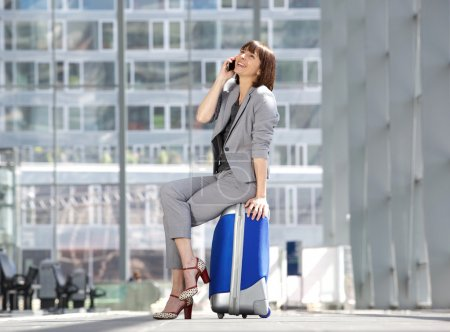 Cheerful business woman talking on mobile phone