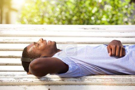Photo pour Gros plan portrait d'un jeune homme afro-américain heureux allongé sur un banc de parc avec écouteurs - image libre de droit