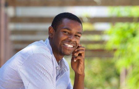 Photo pour Gros plan portrait d'un noir souriant utilisant un téléphone portable à l'extérieur - image libre de droit