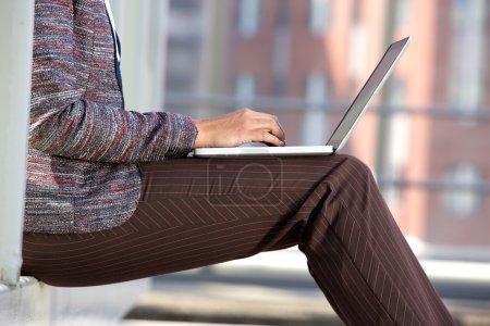 Photo pour Portrait latéral d'une femme d'affaires tapant sur ordinateur portable à l'extérieur - image libre de droit