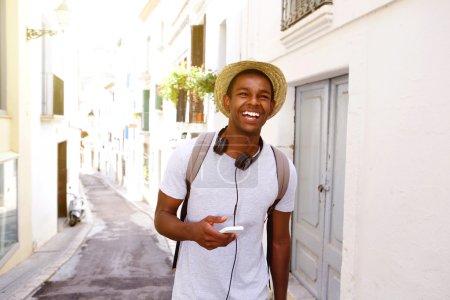 Foto de Retrato de un feliz viajero hombre caminando en la ciudad con teléfono móvil y bolso - Imagen libre de derechos