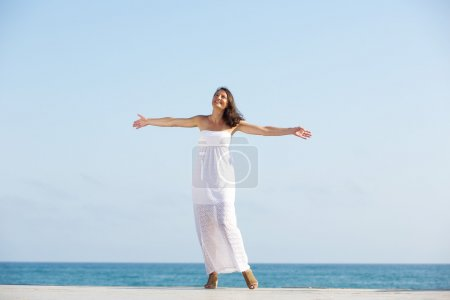Photo for Portrait of a carefree woman enjoying life, standing outdoors with arms outstretched - Royalty Free Image