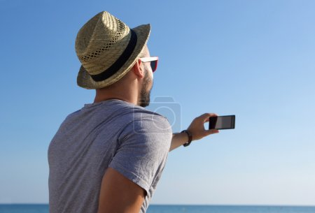 Photo for Young man taking selfie with mobile phone by the sea - Royalty Free Image
