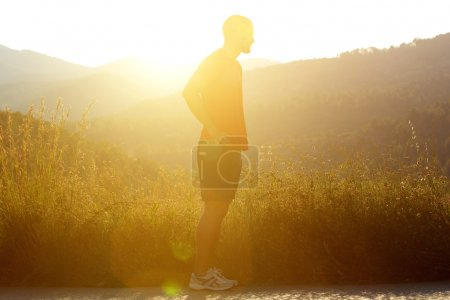 Silhouette male jogger standing outside