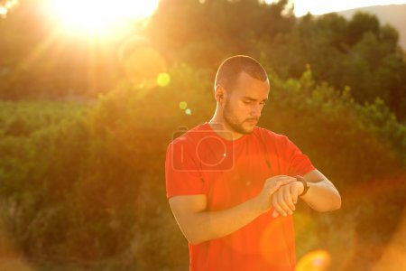 Runner standing outside looking at watch
