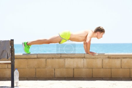 Young fitness man push up workout