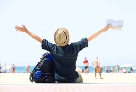 Travel man sitting by beach with arms outstretched