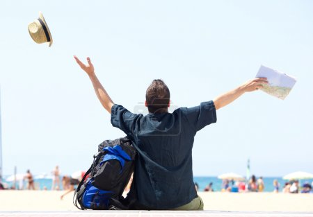 Photo for Happy man with bag and map arrives at beach - from behind - Royalty Free Image