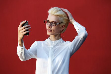 Beautiful blond woman looking at mobile phone