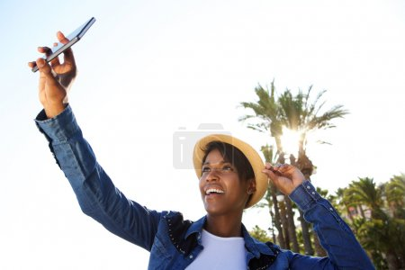 Smiling young african american woman taking selfie outside
