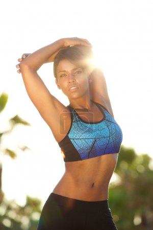 Attractive african american woman stretching muscles outside