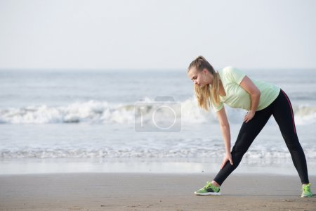 Sporty young woman bend down stretching at the beach