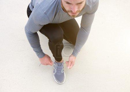 Man tying sport shoe shoelace