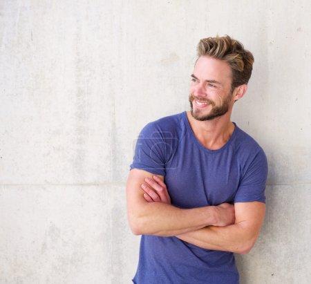 Photo pour Portrait d'un gars souriant confiant avec la barbe posant avec les bras croisés - image libre de droit
