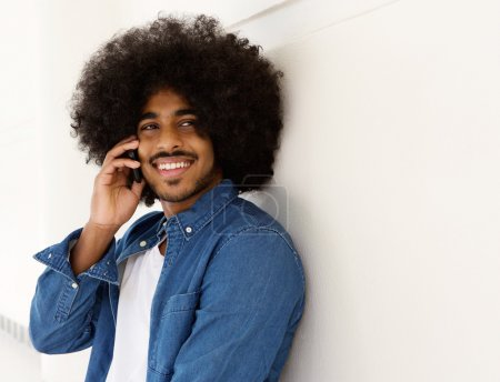 Smiling black man listening on mobile phone